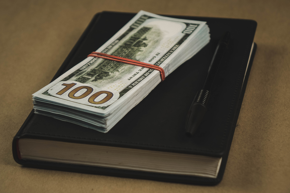 A black notebook , a pen and dollar cash banknotes on wooden background - concept of financial management or planning, make money from freelance writing